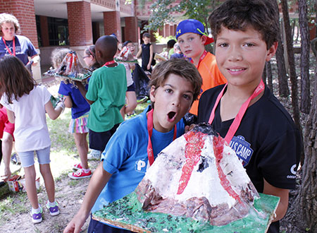 Two kids holding a model volcano