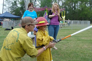 A firefighter helping a child shoot a small fire hose