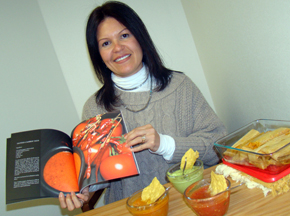 Patty Baker holding her book salsa bowls chips and tamales