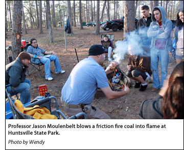 Professor Jason Moulenbelt blows a friction fire coal into flame at Huntsville State Park