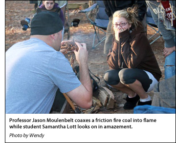 Professor Jason Moulenbelt coaxes a friction fire coal into flame while student Samantha Lott looks on in amazement