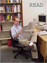 Brian Weis staying current with the news by reading a newspaper.