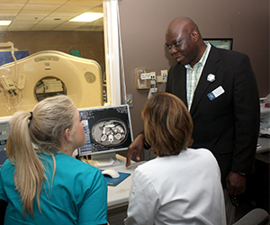 Dr. Francis Ozor and students using the computed tomography scan