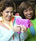two girls playing arcade games with a pink gun