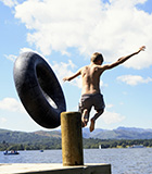 boy jumping off a pier into a lake with an inner-tube