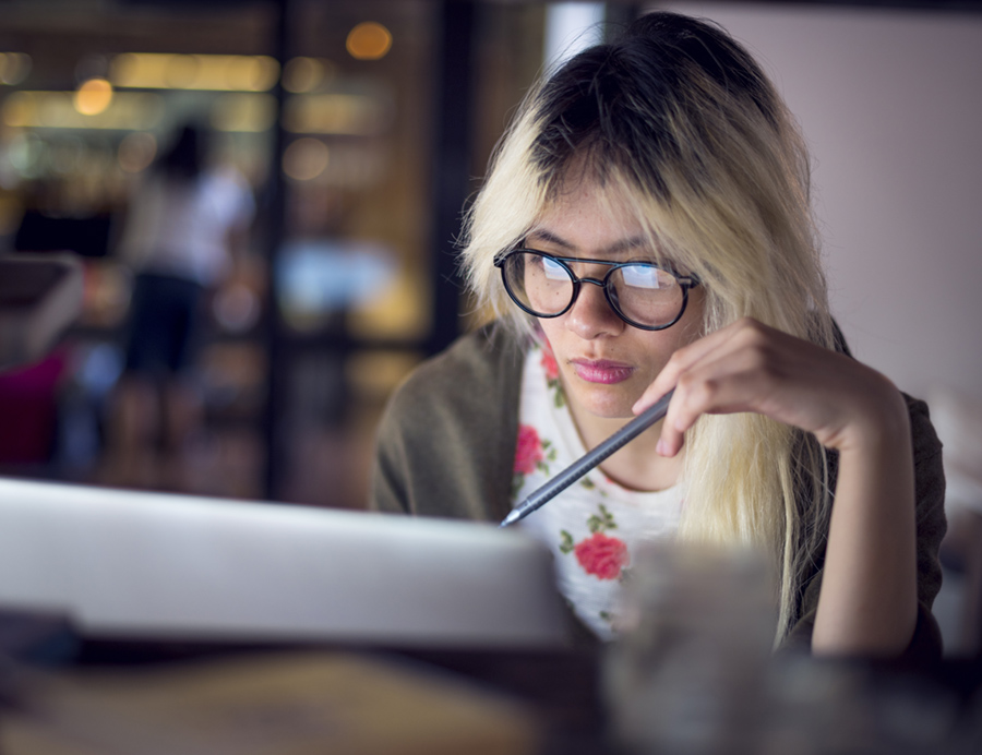 girl with glasses looking at a laptop screen