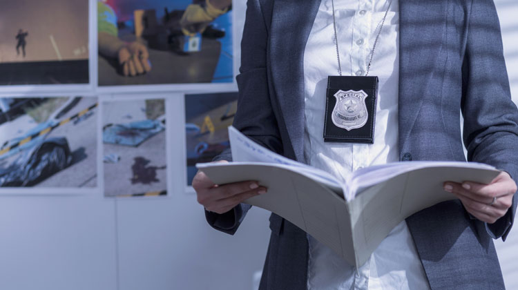 Woman wearing a badge looking over case documents