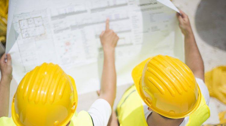 Two people wearing hard hats while inspecting plans