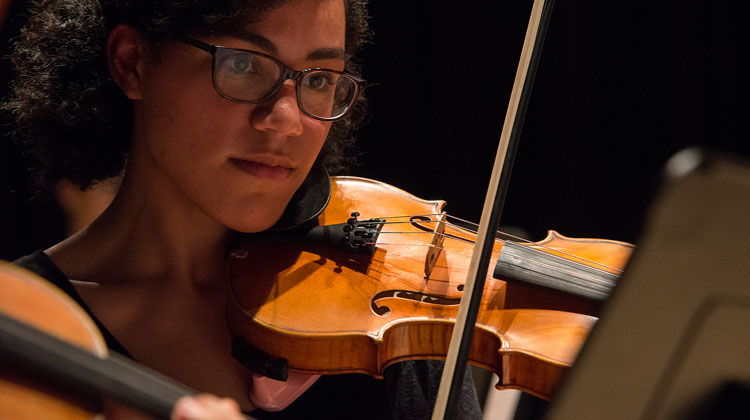 Close up of a woman wearing glasses playing a violin
