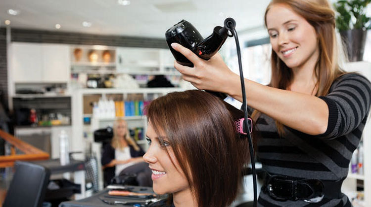 Hair dresser holding a hair dryer with aclient