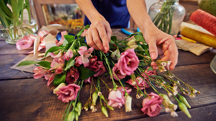 Florist working with a bouquet on a table