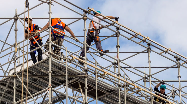 Construction workers walking on a scaffolding