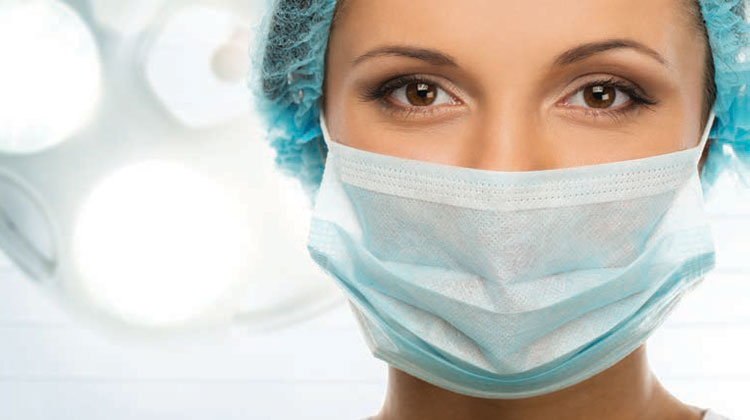 Close up of a woman wearing a hair net and breath mask