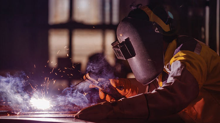 Welder wearing a mask and gloves.