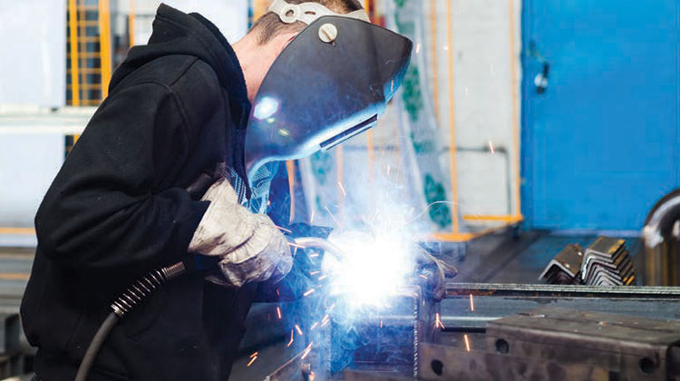 Welder working while wearing mask and gloves.