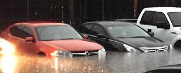 photo of flooded apartment complex parking lot with flooded cars