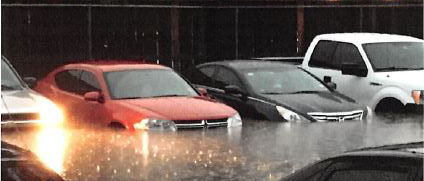 Photo of flooded apartment parking lot with cars