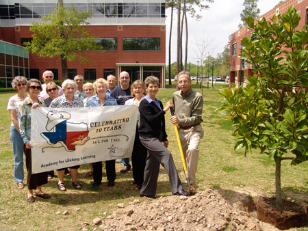 Helen Bostock, chair of the Academy for Lifelong Learning (ALL) at Lone Star College-Montgomery, shovels dirt with Tim Welbes, co-president of The Woodlands Development Company, during the planting of a magnolia tree in honor of ALL's 10th anniversary. Past chairs and ALL members look on during the ceremony, which was generously underwritten by The Woodlands Development Company.