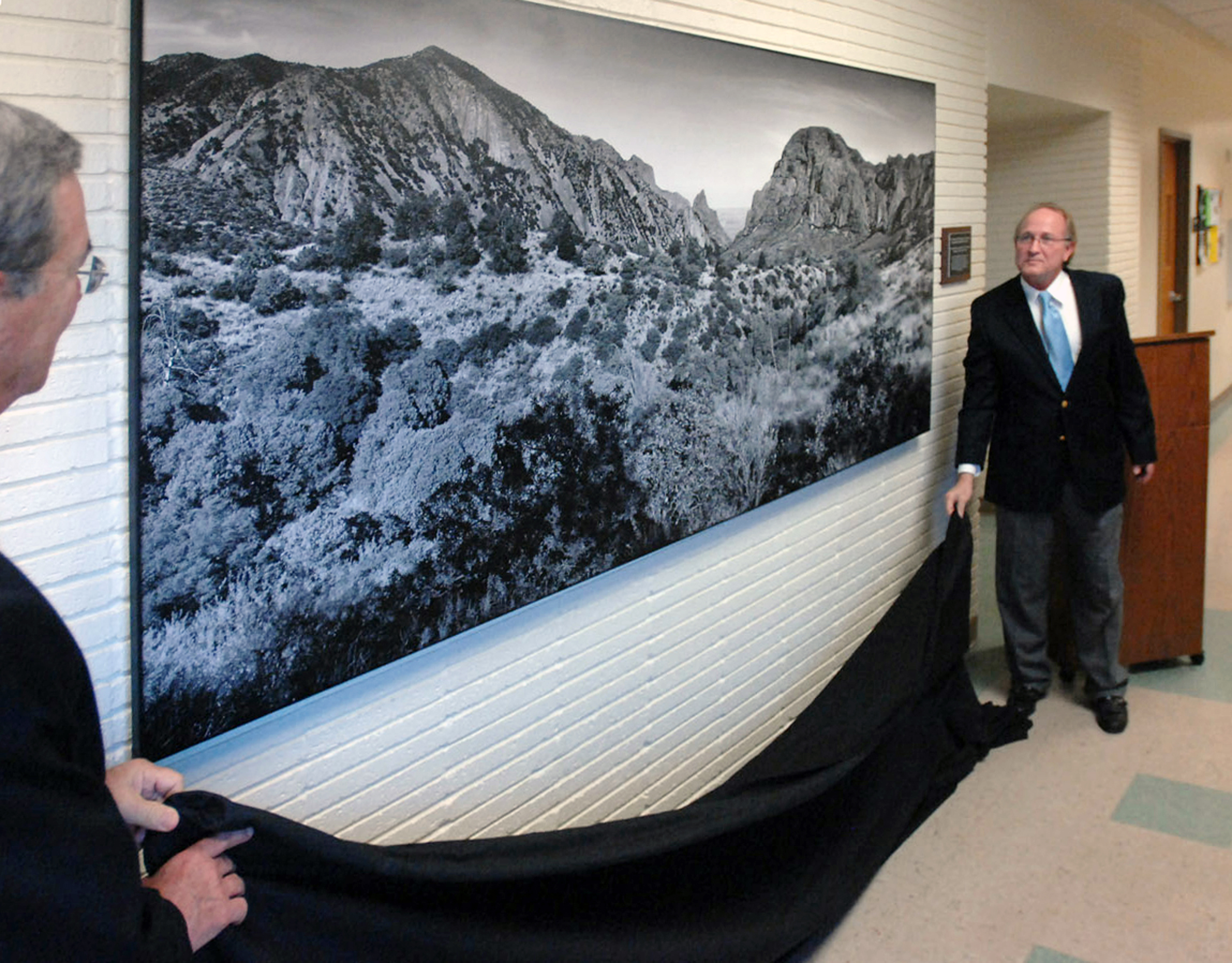 Two representatives from Lamar University undrape a 9-foot by 4-foot panoramic photograph of Big Bend National Park, taken by Richard Ashmore, geology instructor at Lone Star College-Montgomery. Ashmore was commissioned by Lamar to produce the image.