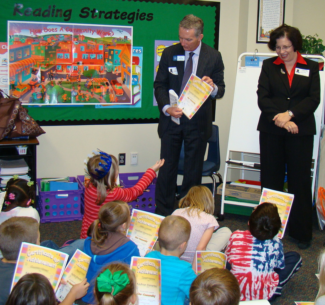 Rand Key and Dr. Julie Leidig, executive administrators from the Lone Star College System, present second-graders at Kaufman Elementary certificates marking their participation in the Junior Achievement program. Key and Leidig were among 40 students, staff, and faculty members from Lone Star College-Montgomery who taught the elementary students.