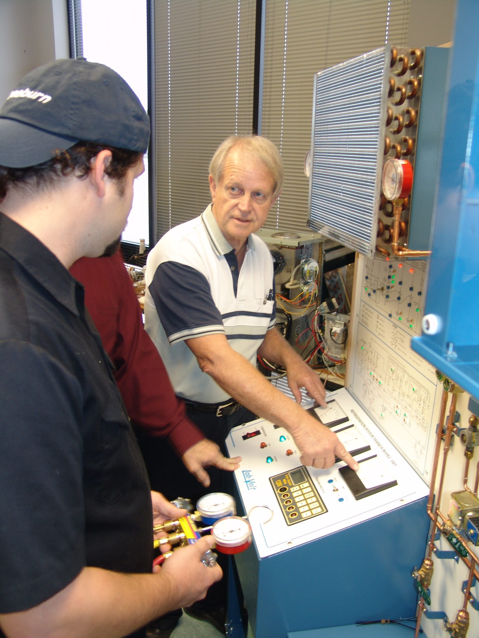 Instructor Robert Watts shows his students some of the technical aspects of testing a cooling system.